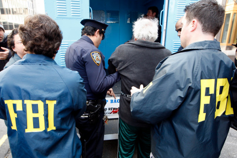Law enforcement officers escort people to be arraigned after indictment in New York