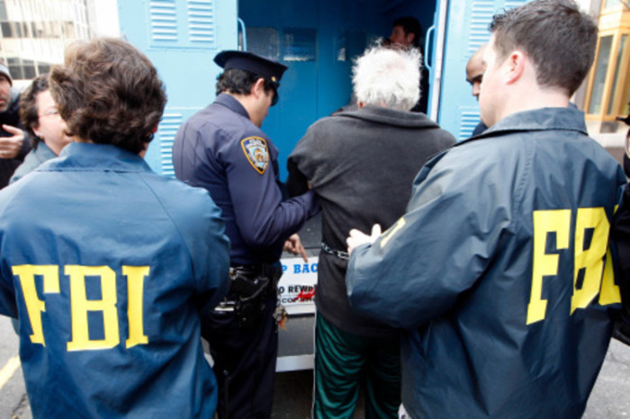 Law enforcement officers escort people to be arraigned after the indictment of over 80 members of organized crime families on charges related to racketeering, conspiracy, extortion, theft, illegal gambling, loan-sharking and embezzlement in New York February 7, 2008. Police in the United States and Italy arrested 77 suspected members of the Mafia on Thursday, including some of its most wanted leaders, for an array of crimes going back more than 30 years. REUTERS/Chip East (UNITED STATES)