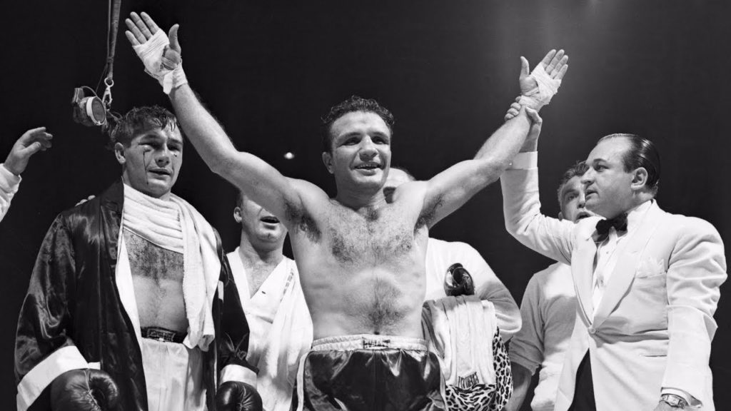 Billy Fox looks happy with his arms raised as he is pronounced the winner with Jake LaMotta looking bloodied behind him.