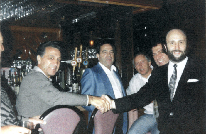 In a photo seized during a 1988 raid, mob boss John DiFronzo (far left) is seen shaking hands with a restaurateur. Marco D'Amico can just be seen peeking over the owner's shoulder.