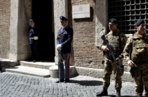 Soldiers and police officers stand guard outside the Italian national anti-mafia services HQ in Rome.